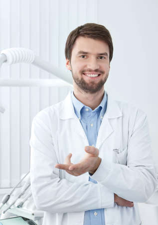 male dentist: Smiley dentist welcomes the patient Stock Photo