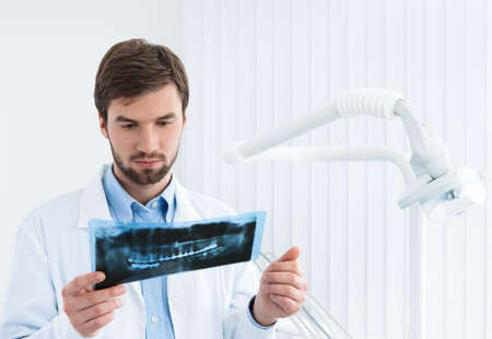 profundity: Dentist carefully examines the roentgenogram, whte background.