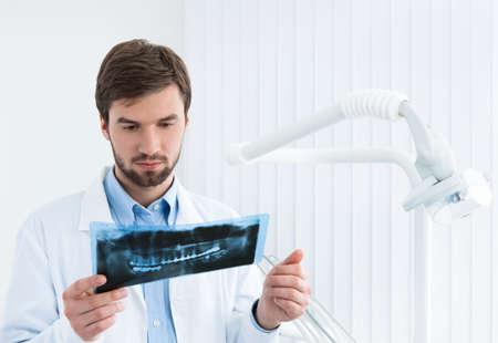 pensiveness: Dentista esamina attentamente l', sfondo whte roentgenogram. Archivio Fotografico