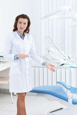 Beautiful doctors assistant shows the dentists chair and explain its work photo