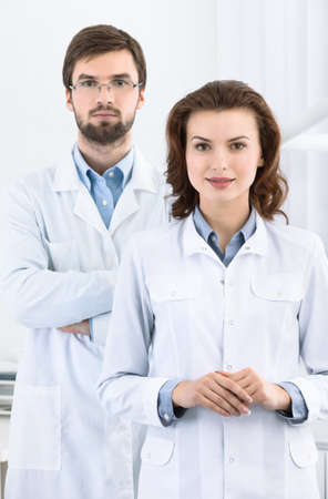 stomatologist: Dentist and his assistant are always ready to help to the patient, white background
