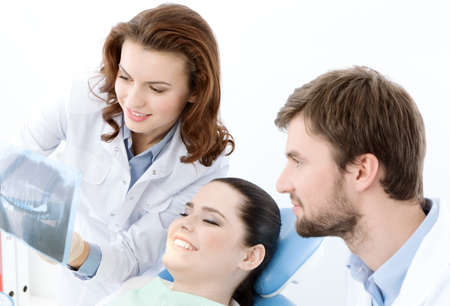 � fond: Le patient examine soigneusement la photo � rayons X de ses dents. Elle est heureuse que tout est ok Banque d'images