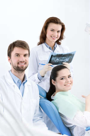 Dentist, assistant and client are satisfied of their work performed photo