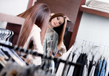 Woman admires herself at the mirror in the store while trying on a wonderful dress photo