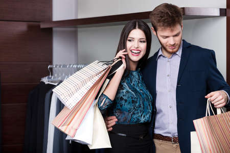 Couple does shopping at the sale shop with great variety of clothes photo