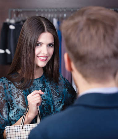 Smiling girl speaks to shop assistant photo