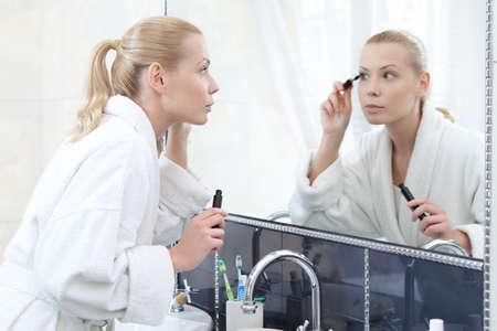 dressing: Pretty woman mascaras her eyelashes in bathroom