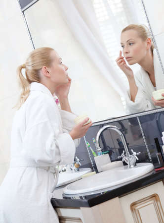 spiegels: Mooie vrouw crèmes haar gezicht in de badkamer