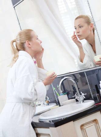look in mirror: Pretty woman creams her face in bathroom
