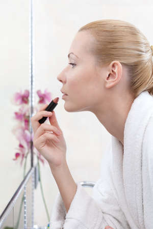 bathroom mirror: Woman makes up in bathroom