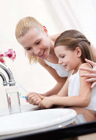 bathroom woman: Little girl cleans her teeth with her mum