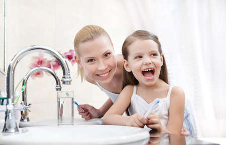 Little girl brushes her teeth with her mother photo