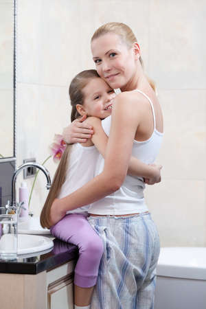 Mother and daughter are in bathroom photo