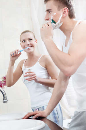 Husband and wife brush their teeth and shave in the bathroom Stock Photo - 14866777