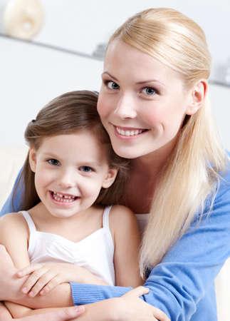 fond of children: Smiley mom hugs her daughter Stock Photo