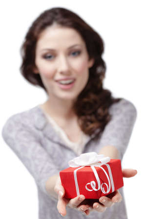 Young woman offers a present wrapped in red paper, isolated on white photo