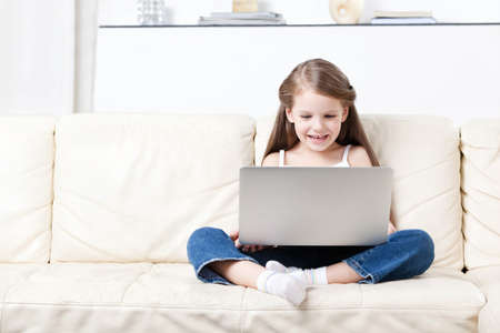Little child surfs on the internet sitting on the white leather sofa