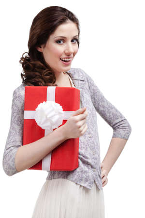 Young woman hugs a gift wrapped in red paper, isolated on white photo