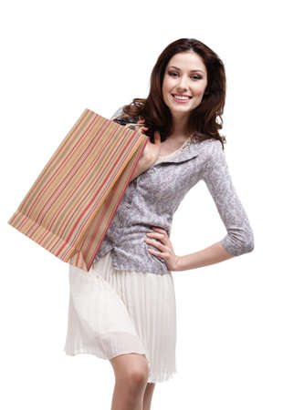 hands on hip: Happy woman keeps striped paper gift bag, isolated on white