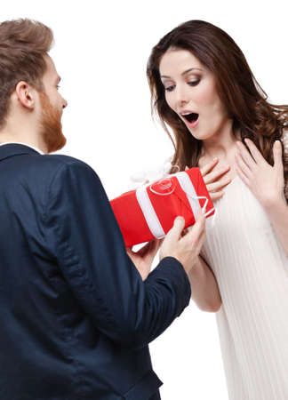 Man surprises his girlfriend with present wrapped in red paper, isolated on white photo