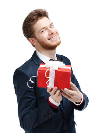 welcome party: Handsome man offers a present wrapped in red gift paper, isolated on white