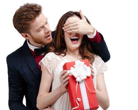 closes eyes: Man closes eyes of his girlfriend, isolated on white Stock Photo