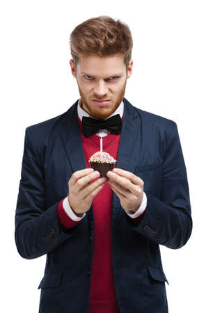 unkind: Angry man in blue suit with bow tie holds small tart, isolated on white Stock Photo