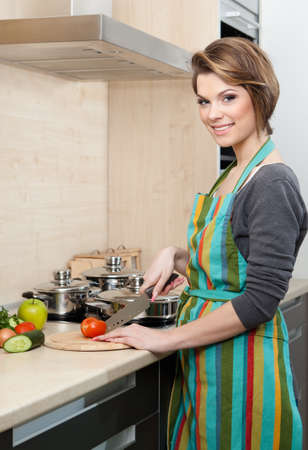 Beautiful woman in striped apron chops vegetables in the kitchen photo