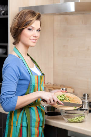 Beautiful woman in striped apron cuts vegetables in the kitchen photo