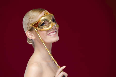 Smiley woman with masquerade mask, isolated on purple photo