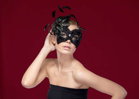 Beautiful woman with black masquerade mask with feathers, isolated on purple photo