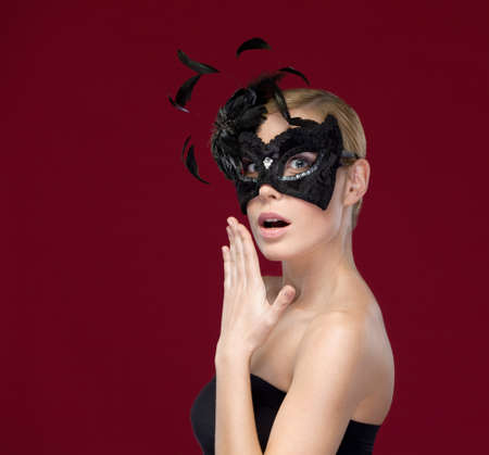 enigma: Pretty girl with black masquerade mask with feathers, isolated on purple Stock Photo