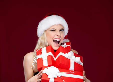 Pretty woman in Christmas cap holds a set of presents, isolated on purple Stock Photo - 14866448