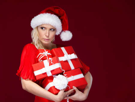 Attractive woman in Christmas cap holds a set of presents wrapped with red paper, isolated on purple photo