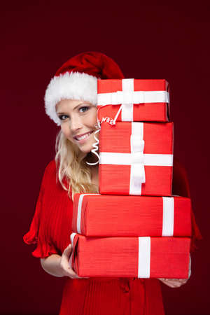 Attractive girl in Christmas cap hands a set of presents wrapped with red paper, isolated on purple photo