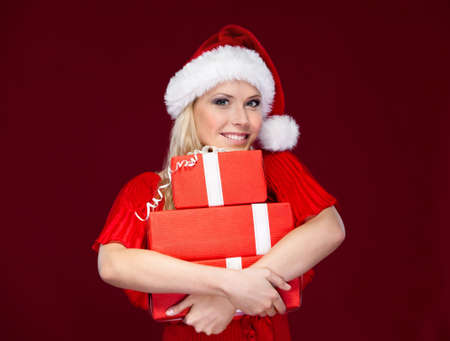 gladly: Young woman in Christmas cap hands a set of presents wrapped with red paper, isolated on purple