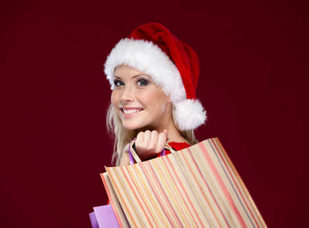 Beautiful woman in Christmas cap hands shopping packets, isolated on purple photo