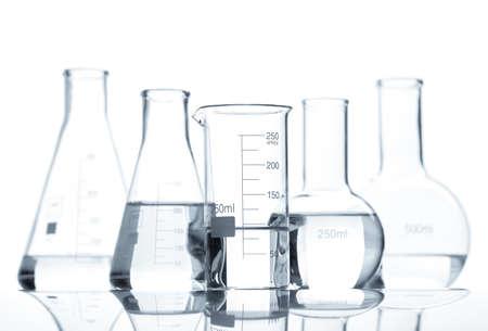 beaker: Cinco matraces de laboratorio clásicas con un líquido transparente, aislado