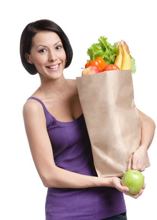 Vegetarian young woman with the packet full of different healthy food, isolated, white background photo