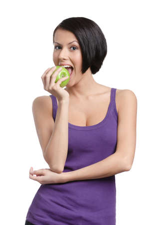 Young lady tastes a green apple, isolated, white background Stock Photo