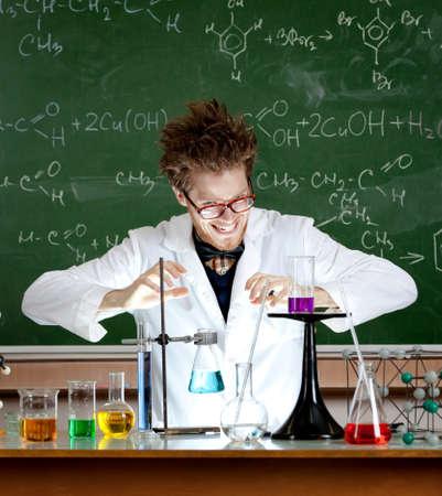 gladly: Riendo profesor loco combina algunos l�quidos en su laboratorio Foto de archivo