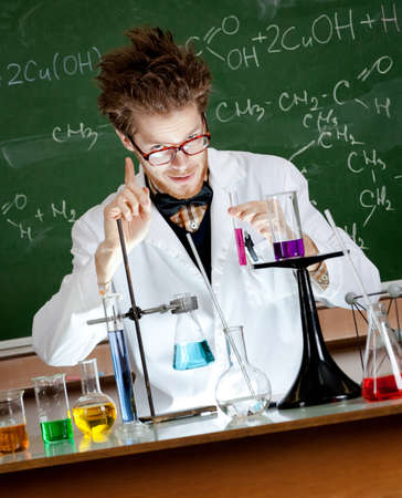 schoolhouse: Mad professor gestures forefinger while conducting an experiment in his laboratory Stock Photo
