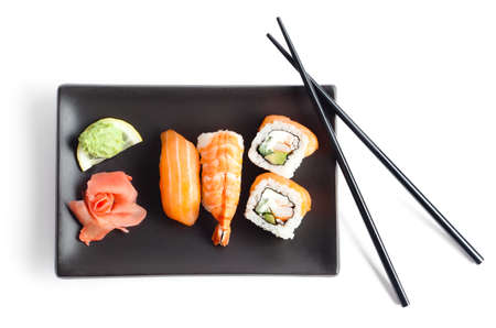 sushi plate: Black plate with sushi and chopsticks, isolated Stock Photo