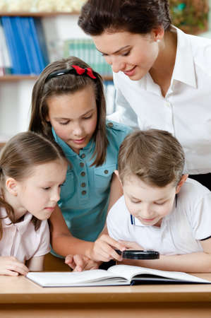 adult intercourse: Young teacher with her pupils examine something with magnifying glass Stock Photo
