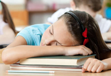 Tired schoolgirl sleeps at the desk, close up photo