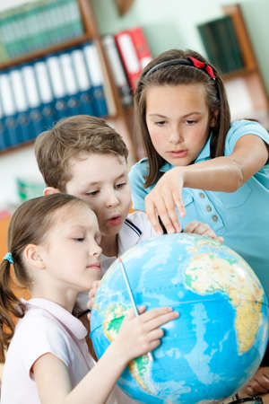 pry: Friendly classmates help to each other to find something at the terrestrial globe. Schooling process Stock Photo