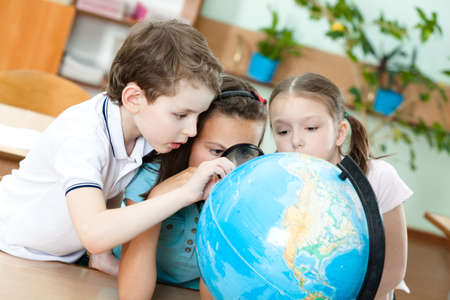 pry: Three friends examine a school terrestrial globe Stock Photo