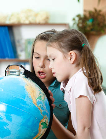 Two schoolgirls look at the globe in wide-eyed astonishment photo
