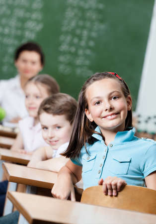 Smiley schoolgirl sits at the desk at math lesson photo
