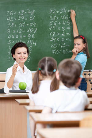 four classes: math teacher questions pupils at the chalkboard Stock Photo